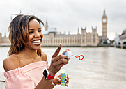 UK, London, happy woman making soap bubbles near Palace of Westminster - MGOF03631