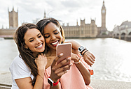 UK, London, two happy women with smartphone near Westminster Bridge - MGOF03634