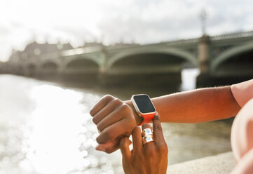 UK, London, close-up of woman using her smartwatch near Westminster Bridge - MGOF03637