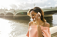 UK, London, woman talking on the phone near Westminster Bridge - MGOF03640