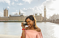 UK, London, beautiful woman taking a picture near Westminster Bridge - MGOF03643