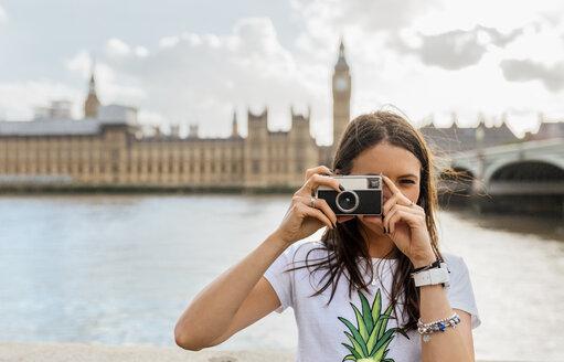 UK, London, beautiful woman taking a picture near Westminster Bridge - MGOF03646
