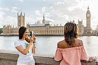 UK, London, woman with friend taking a picture near Palace of Westminster - MGOF03649