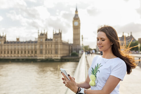 UK, London, woman sending messages with her smartphone on Westminster Bridge - MGOF03652