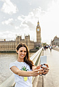 UK, London, beautiful woman taking a selfie on Westminster Bridge - MGOF03655