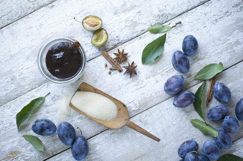 Preserving jar of plum jam and ingredients on wood - ASF06118