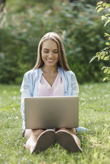 Smiling young woman using laptop on a meadow - VPIF00140