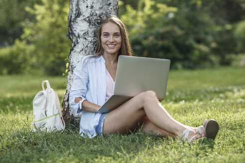 Portrait of smiling young woman using laptop on a meadow - VPIF00146