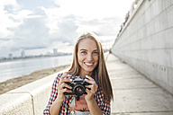 Smiling young woman with a camera at the riverside - VPIF00161