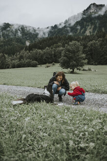 Austria, Vorarlberg, Mellau, mother and toddler with dog on a trip in the mountains - DWF00304