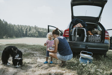 Mother and toddler with dog at a car on the countryside - DWF00319