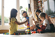 Family playing with building blocks on the floor together - JUBF00257