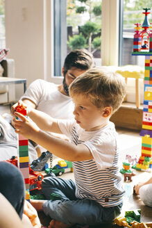 Boy with his family stacking building blocks on the floor - JUBF00260