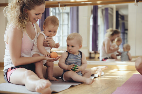 Mother with playing twin babies sitting on yoga mat - MFF04000