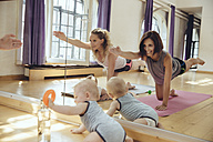 Two mothers working out on yoga mats with babies playing around them - MFF04003