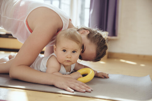 Mother kissing her baby while working out on a yoga mat - MFF04009