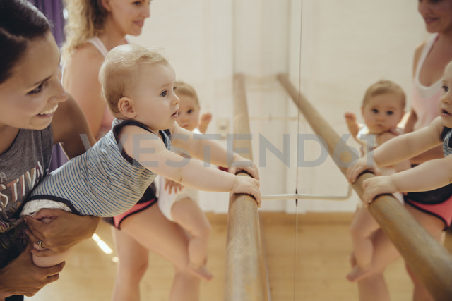 Two mothers holding up their small children to barre in dance studio - MFF04015