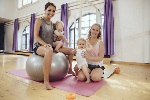 Portrait of happy mothers and babies in exercise room - MFF04024