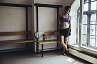 Sporty pregnant woman standing in locker room looking out of window - MFF04036