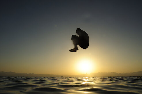 Man jumping into the sea at sunset - ECPF00136