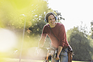 Portrait of smiling man with racing cycle listening music with headphones in a park - UUF11741