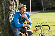 Portrait of laughing man with racing cycle leaning against tree trunk in a park - UUF11753