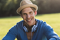 Portrait of laughing man with hat and headphones in a park - UUF11759