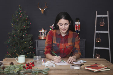 Young woman drawing Christmas card with pencil - RTBF01013