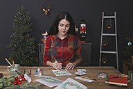Young woman painting Christmas card with water colors - RTBF01019