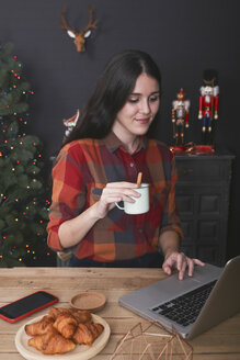Smiling woman with cup of coffee using laptop at Christmas time - RTBF01022