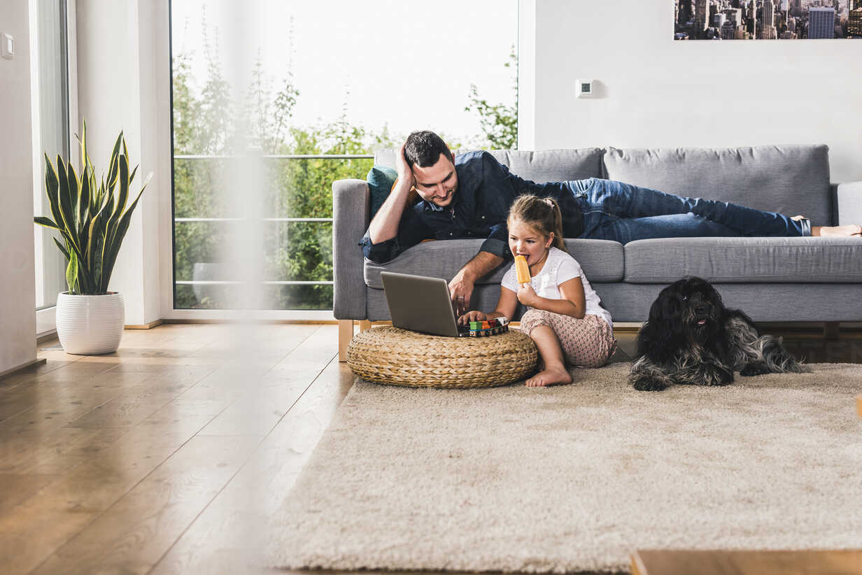Father using laptop at home with his little daughter - UUF11775 - Uwe Umstätter/Westend61