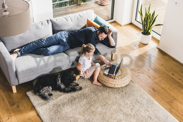 Father using laptop at home with his little daughter - UUF11778