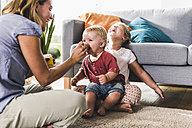 Mother feeding kids in living room - UUF11793