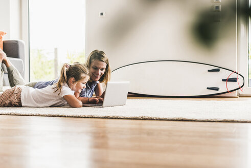Mother and daughter using laptop, lying on carpet - UUF11799