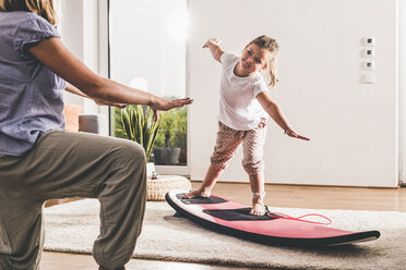 Mother and daughter exercising with surfboard in living room - UUF11805