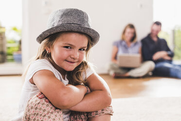 Little girl with hat, parents using laptop in background - UUF11814
