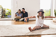 Little girl with hat having fun at home, parents using laptop in background - UUF11820