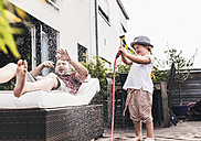 Fathercand daughter in the garden, daughter splashing water with hose - UUF11829