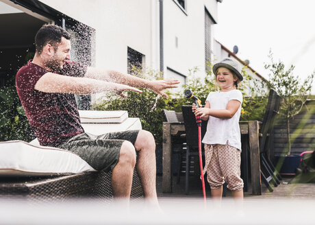 Fathercand daughter in the garden, daughter splashing water with hose - UUF11832