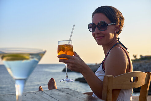 Italy, Santa Caterina, portrait of relaxed woman toasting with glass of Spritz at sunset - DIKF00274