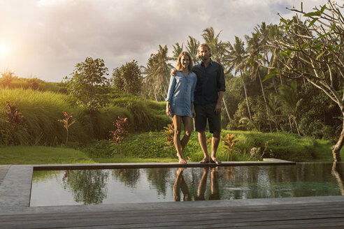 Smiling couple standing on the edge of a pool in lush tropical garden - SBOF00796