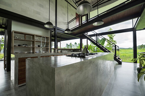 Modern minimalist kitchen in contemporary design house with glass facade surrounded by lush tropical garden - SBOF00799