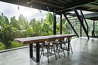 Modern wooden table in contemporary design house with glass facade surrounded by lush tropical garden - SBOF00805