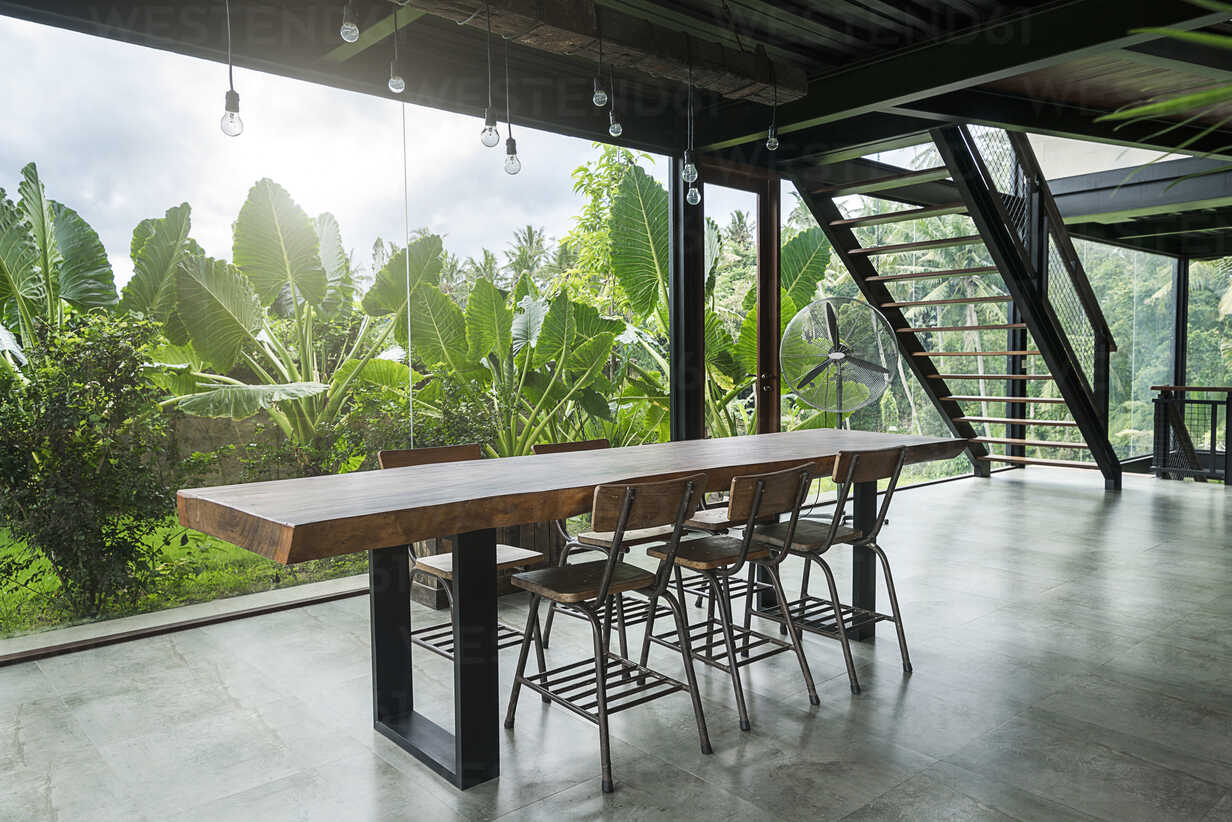 Modern wooden table in contemporary design house with glass facade surrounded by lush tropical garden - SBOF00805 - Steve Brookland/Westend61
