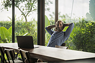 Handsome man with laptop sitting at modern wooden table in contemporary design house - SBOF00811