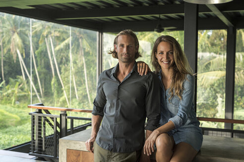 Couple smiling at camera in contemporary design house with glass facade surrounded by lush tropical garden - SBOF00817