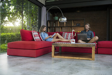 Couple with laptop and book relaxing on red couch in modern living room with glass facade - SBOF00820