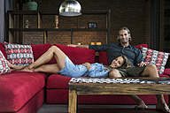 Smiling couple relaxing on red couch in modern living room - SBOF00823