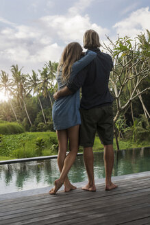 Hugging couple standing on wooden terrace in front of pool and enjoying stunning view of sunset in lush tropical garden - SBOF00826