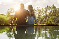 Embracing couple sitting on the edge of a pool and enjoying stunning view of sunset in lush tropical garden - SBOF00829
